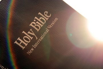 Holy Bible with lens flare and rainbow.