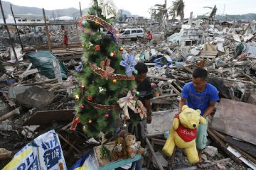 A typhoon survivor decorates a Christmas tree amidst the rubble of destroyed houses in Tacloban city in central Philippines December 17, 2013. Super typhoon Haiyan reduced almost everything in its path to rubble when it swept ashore in the central Philippines on November 8, killing at least 6,069 people, leaving 1,779 missing and 4 million either homeless or with damaged homes. REUTERS/Erik De Castro (PHILIPPINES - Tags: DISASTER ENVIRONMENT SOCIETY TPX IMAGES OF THE DAY) ORG XMIT: EDC809
